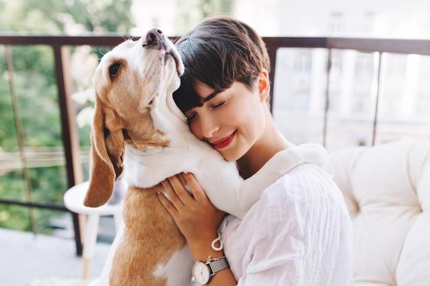눈을 가진 재미있는 비글 강아지를 껴 안은 짧은 갈색 머리를 가진 기쁘게 소녀의 클로 우즈 업 초상화 폐쇄