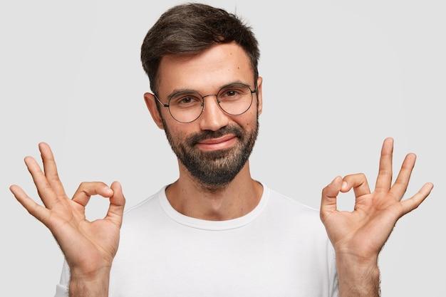 幸せな表情で喜んで無精ひげを生やした若い男性の肖像画をクローズアップ、暗いひげと口ひげを生やし、大丈夫なジェスチャーを行い、状況を制御し、白い壁に隔離されます。ボディーランゲージの概念