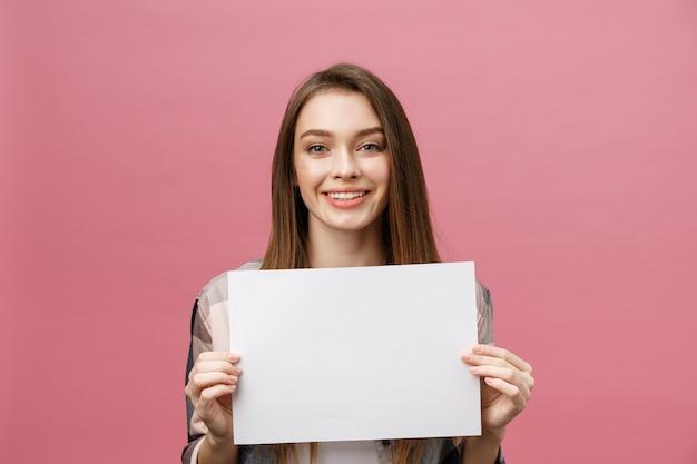 笑顔と白い大きなモックアップポスターを保持しているポジティブな笑いの女性の肖像画を閉じる