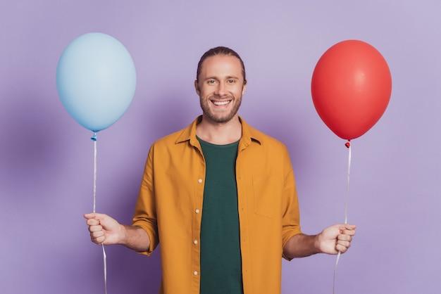 Крупным планом портрет позитивного человека, сияющего улыбкой, держит два воздушных шара на фиолетовой стене