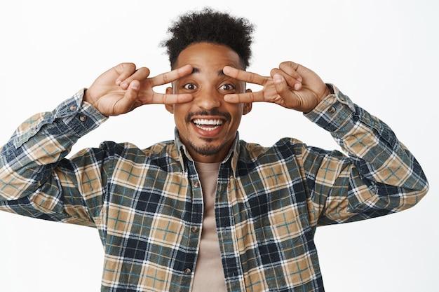 Крупным планом портрет позитивного, улыбающегося афро-американского студента, парня, показывающего жест мира с v-образным знаком и смотрящего счастливым, в клетчатой рубашке на белом