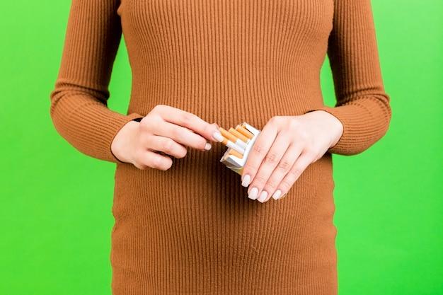 녹색 배경에 담배 한 갑을 들고 갈색 드레스에 임신한 여자의 초상화를 닫습니다. 임신 중 해로운 습관.