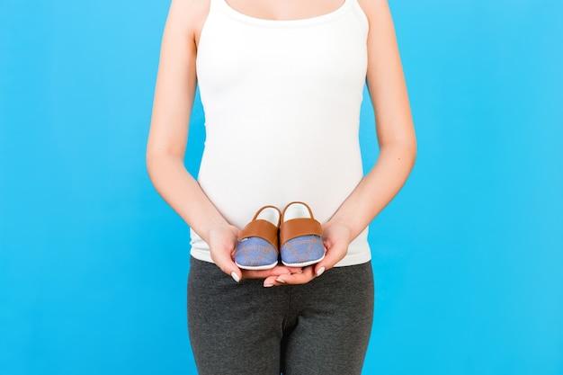 赤ちゃんの男の子のためのブーツを保持している家庭用衣類の妊娠中の女性の肖像画を間近します。