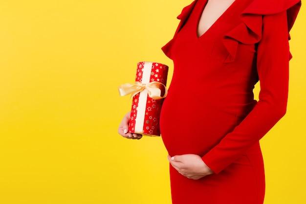 노란색 표면에 선물 상자를 들고 빨간 드레스에 임신 한 여자의 초상화를 닫습니다