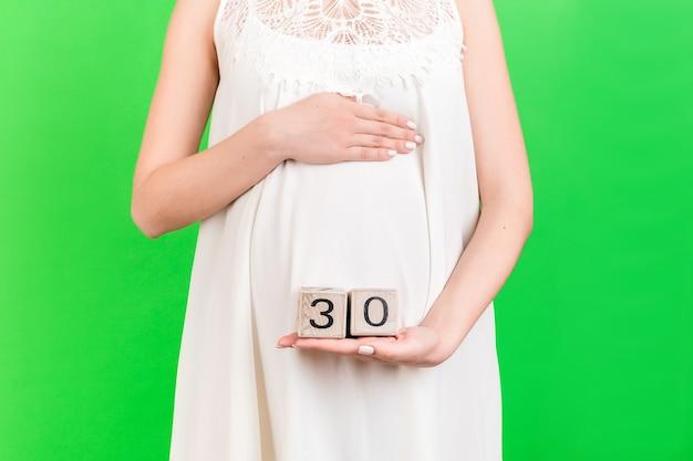 큐브를 보여주는 흰 드레스에 임신한 여자의 초상화를 닫습니다