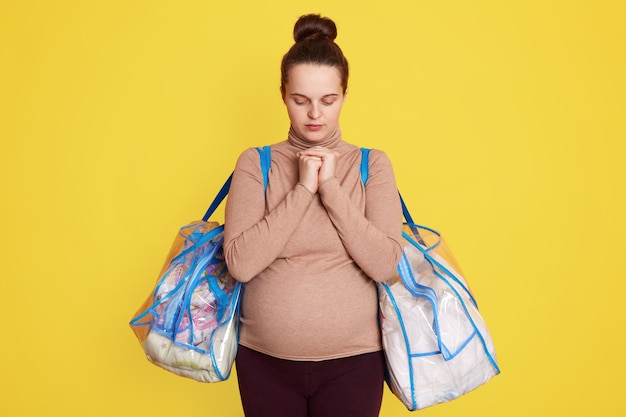目を閉じてポーズをとる、カジュアルな服装をしている、髪のお団子を持っている、拳を一緒に保ち、赤ちゃんの健康を祈って、横になっている病院に行く準備ができている妊婦の肖像画をクローズアップします。