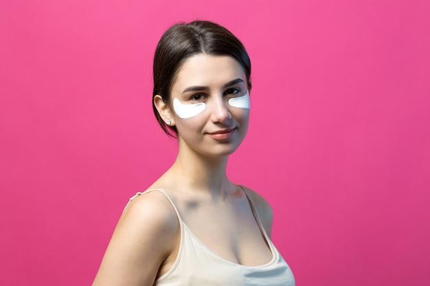 目の下のパッチを使用して裸の肩を持つかなり魅力的な女の子の肖像画をクローズアップ。ピンクの背景の上に立っています。