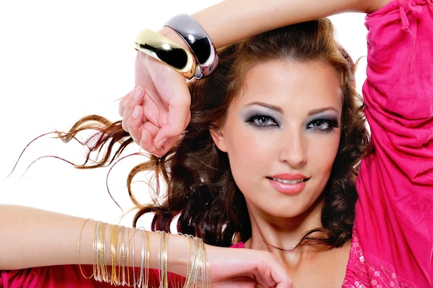 明るいメイクとスタイリッシュなブレスレットを持つかなり美しい女性のクローズアップの肖像画