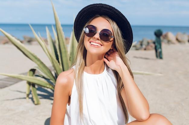 長い髪のかわいいブロンドの女の子のクローズアップの肖像画は、海の近くのビーチに座っています。彼女はカメラに微笑んでいます。