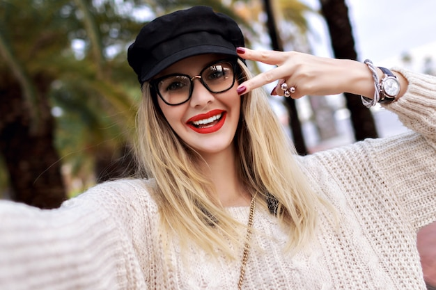 トレンディなカジュアルな服装、赤い口紅、透明なメガネ、マニキュア、ジュエリーを身に着けているかなりブロンドの女性の肖像画を間近します。驚いた感情、手のひらでポーズ、一人で旅行します。