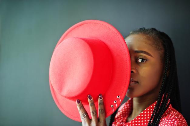 かわいい三つ編みビジネスアフリカ系アメリカ人女性明るい偉そうな人フレンドリーなウェアオフィスの赤いシャツと帽子の肖像画を閉じます。
