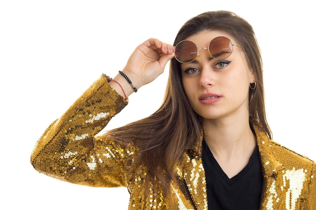 Крупным планом портрет красивой женщины брюнетки в круглых очках и золотой куртке, смотрящей в камеру, изолированную на белом фоне