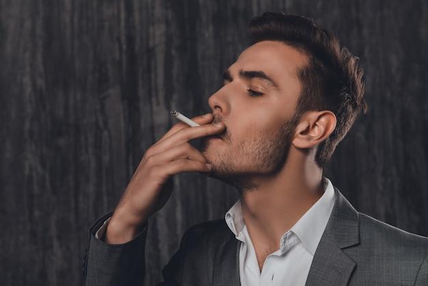 Крупным планом портрет красивого бизнесмена, курящего сигарету