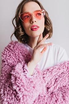 Крупным планом портрет довольно европейской женщины с темными волосами, изолированные на белой стене. эффектная девушка в розовой шубе и забавных очках наслаждается фотосессией.