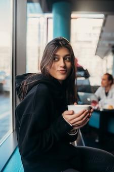 Закройте вверх по портрету довольно женского питьевого кофе. леди держит белую кружку рукой.
