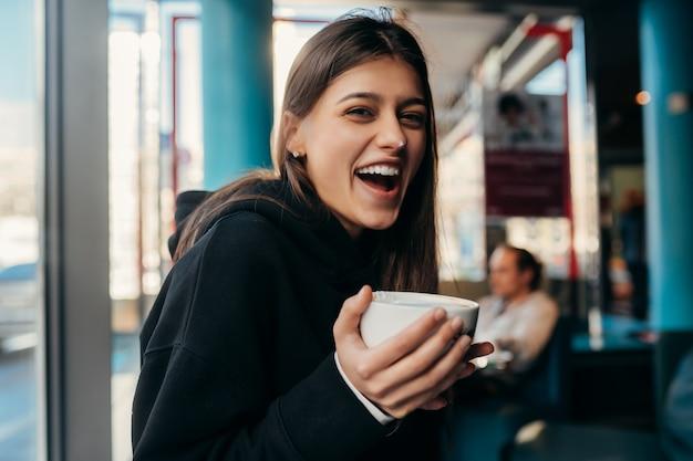 かなり女性がコーヒーを飲むの肖像画を間近します。
