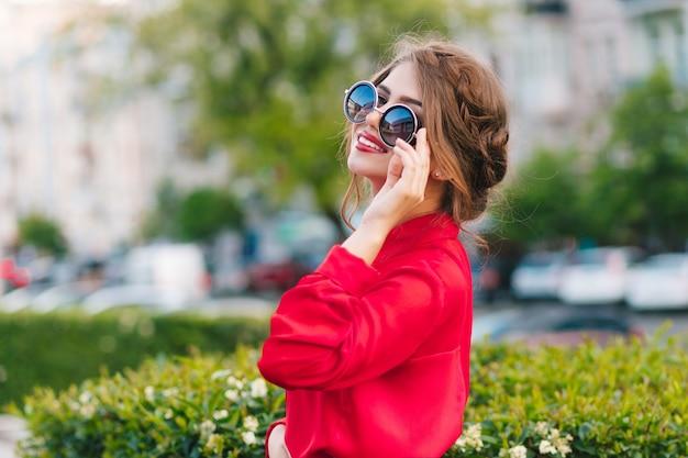 公園でカメラにポーズをとってサングラスでかわいい女の子のクローズアップの肖像画。彼女は赤いブラウスと素敵な髪型を着ています。彼女は遠くを見ています。