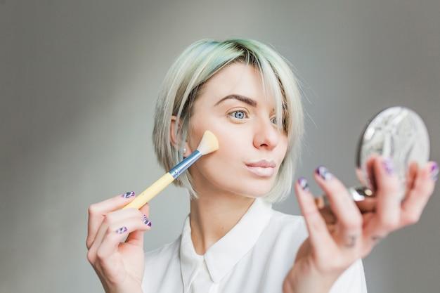 灰色の背景に短い白い髪のかわいい女の子のクローズアップの肖像画。彼女は白いドレスを着て、手にある鏡を見て、顔を粉にします。