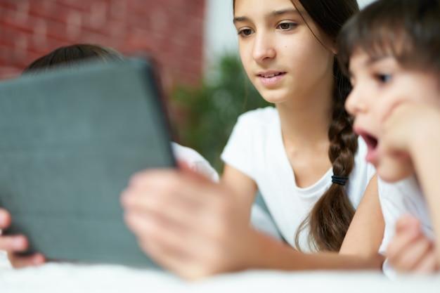 디지털 태블릿을 사용하면서 웃고 있는 예쁜 라틴계 소녀의 초상화를 클로즈업하세요. 십대 자매는 집에서 만화를 보면서 두 명의 남동생을 즐겁게 합니다. 행복한 어린 시절, 기술 개념