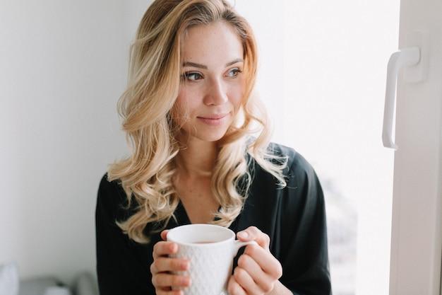 自宅で朝のお茶とかわいい女の子の肖像画をクローズアップ。彼女は窓に座って夢のような目をそらしている