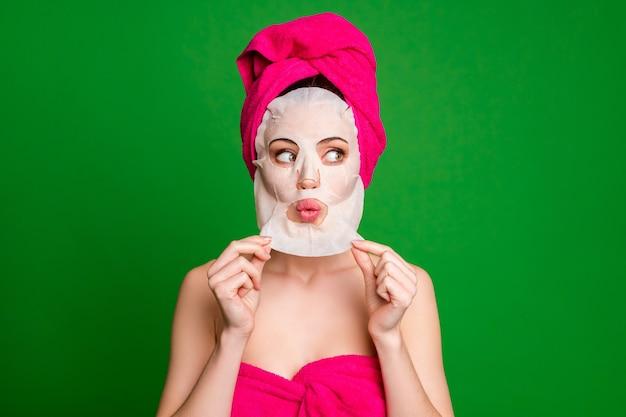 Портрет крупным планом симпатичной женщины в тюрбане, снимающей маску для лица, безупречная кожа надутые губы, изолированные на ярко-зеленом цветном фоне