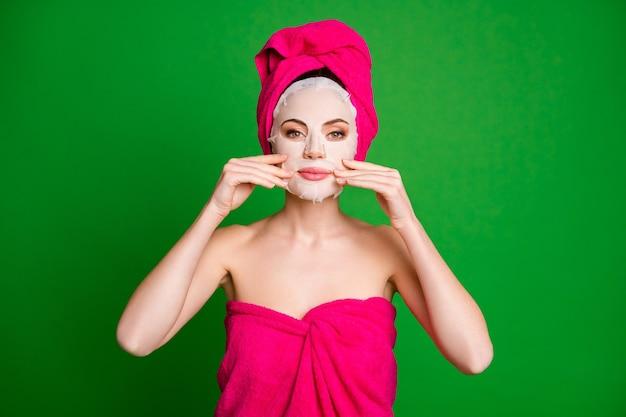 밝은 녹색 배경에 격리된 안면 마스크 미용사 절차를 적용하는 터번을 입은 예쁜 나체 누드 여성의 클로즈업 초상화