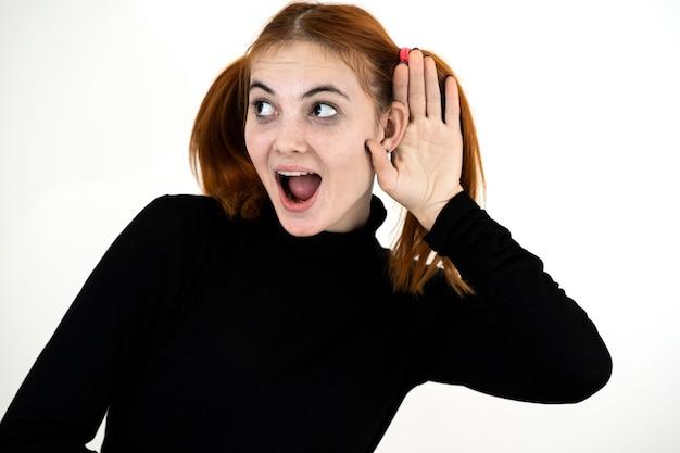 Крупным планом портрет довольно рыжая девочка-подросток, держащая руку к уху, слушая секрет.
