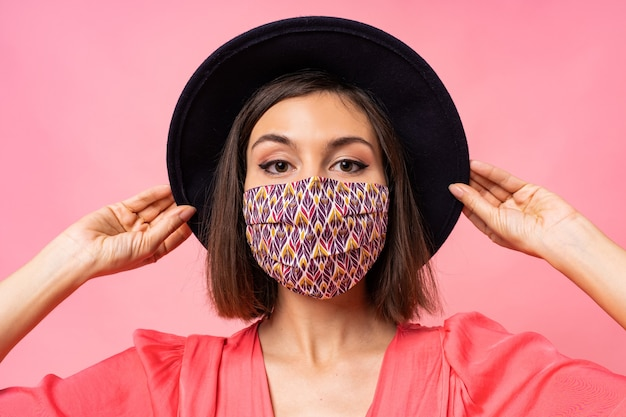 예쁜 여자 옷 보호 세련 된 얼굴 마스크의 초상화를 닫습니다. 검은 모자와 선글라스를 쓰고. 분홍색 벽 위에 포즈