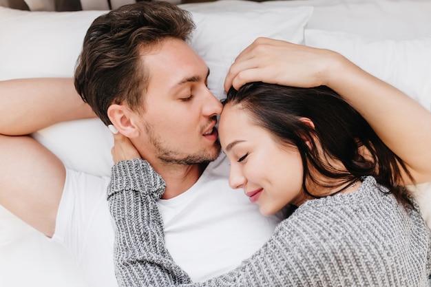 灰色のパジャマを着たきれいな女性のクローズアップの肖像画は、夫と一緒にベッドに横たわっています