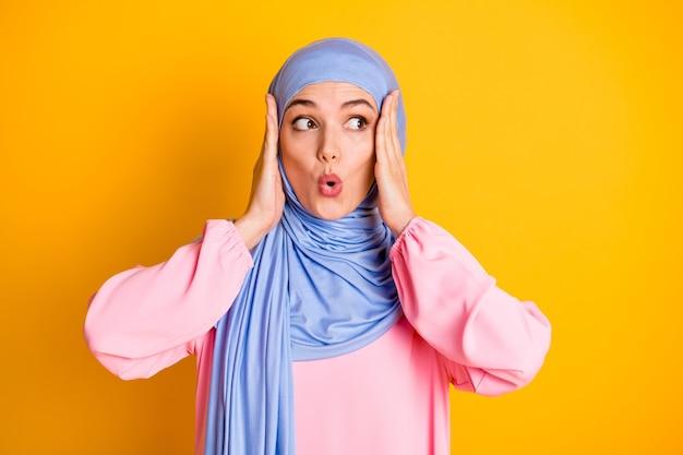 히잡을 쓴 꽤 걱정스러운 이슬람교도의 클로즈업 초상화는 밝은 노란색 배경에 격리된 놀라운 뉴스 입술을 옆으로 바라보고 있습니다.