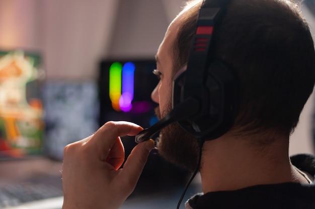 온라인 게임 가상 토너먼트에서 팀원들과 헤드셋으로 이야기하는 프로 e스포츠 선수의 초상화를 닫습니다. rgb 네온 불빛, 디지털 플레이어가 있는 홈 스튜디오 룸