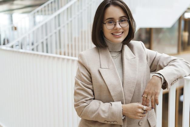 プロの、スマートな若い実業家、会社でキャリアを開始し、階段と笑顔のカメラに寄りかかって、ベージュのジャケットのメガネを着用し、同僚と話している女の子のクローズアップの肖像画。 Premium写真