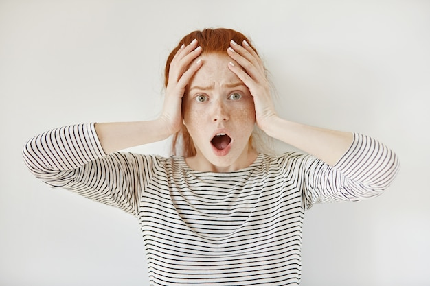困惑して怖がっている赤毛の白人学生の女の子の肖像画を閉じる
