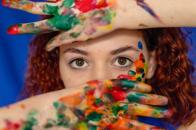 빨간 곱슬 머리 여자의 클로즈 업 초상화 젊은 쾌활 한 페인트에 더러워진. 그녀의 얼굴에 창의적인 패턴이 있는 소녀의 초상화. 예술 또는 여성 블로그를 위한 컨셉 사진