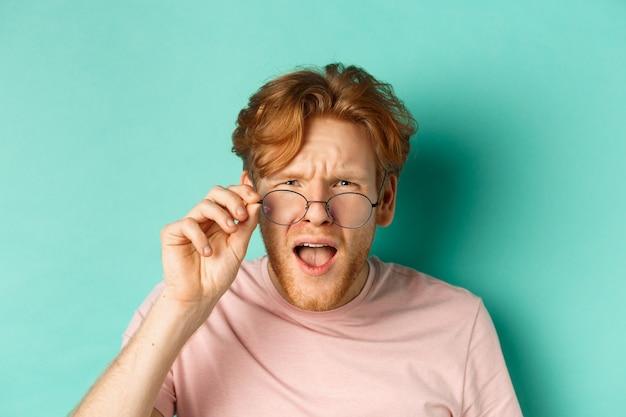 赤毛の男の離陸メガネの肖像画をクローズアップし、ターコイズブルーの背景の上にショックを受けて立っている奇妙な何かに混乱している