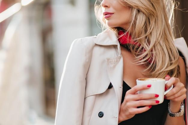 飲み物と白いカップを保持しているコートの洗練された金髪の女性のクローズアップの肖像画。寒い日にコーヒーを飲み、目をそらしている魅力的な金髪の女性。