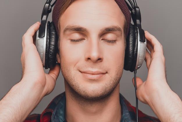 目を閉じて音楽を聴いているヘッドフォンでリラックスした男の肖像画をクローズアップ