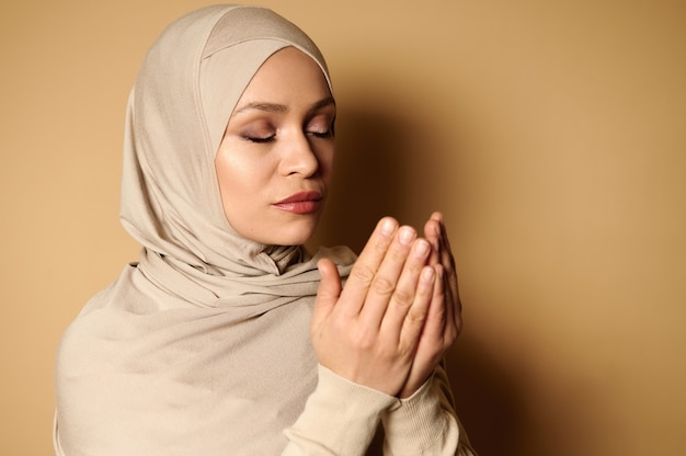 コピースペースでベージュを祈る厳格な服装で宗教的な美しい女性の肖像画をクローズアップ。ラマダンの祈り