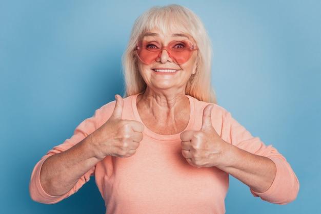 サングラスで引退した女性の肖像画をクローズアップ2つの親指を上げる