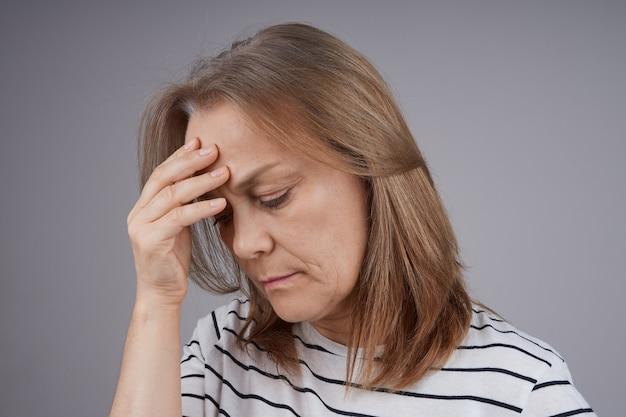 頭痛に苦しんでいる引退した女性の肖像画をクローズアップ