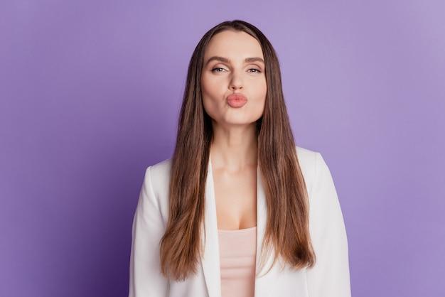 ロマンチックなかわいい女性の肖像画をクローズアップ目を閉じて、紫の壁にポーズをとってエアキスウェアフォーマルスーツを送信します