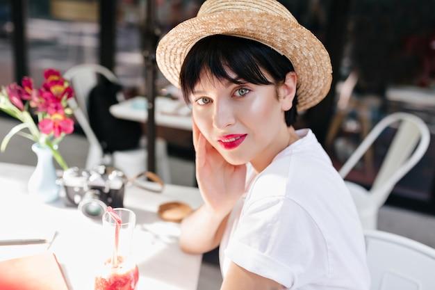 屋外カフェで休んでいる間、光沢のある肌と黒髪のロマンチックな女の子のクローズアップの肖像画
