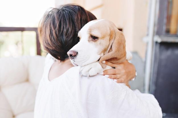 갈색 머리 여자의 어깨 너머로 멀리보고 슬픈 비글 강아지의 클로즈업 초상화