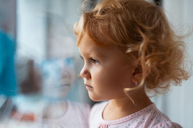 창문을 통해보고 슬픈 아이 여자의 클로즈업 초상화.