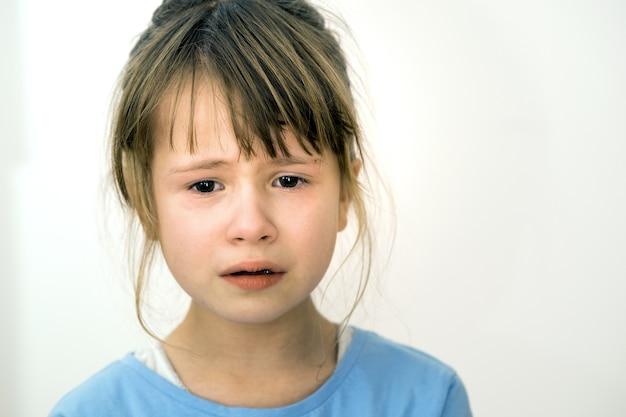 悲しい泣いている子供の女の子の肖像画を閉じる
