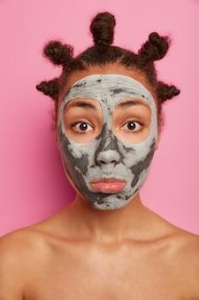 悲しい混血の若い女性のクローズアップの肖像画は、鏡で自分自身を見て、顔に粘土のマスクを適用し、裸の肩で立って、体と顔色を気にし、ピンクの壁に隔離されています。