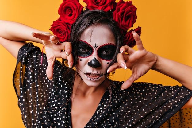 할로윈 메이크업으로 무서운 여자의 클로즈업 초상화입니다. 죽음의 날에 멕시코 복장에 포즈를 취하는 예쁜 여성 모델.