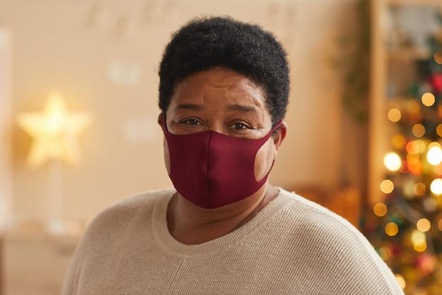 마스크를 쓰고 집에서 크리스마스를 축하하는 동안 카메라를보고 수석 아프리카 계 미국인 여자의 초상화를 닫습니다, 복사 공간
