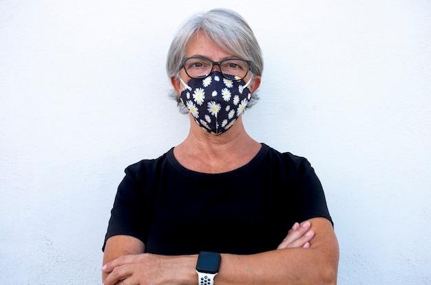 シニア白髪の女性の肖像画をクローズアップコロナウイルスのパンデミックから保護する医療マスクを着用し、covid-19流行の概念の広がりから保護フェイスカバーで深刻な女性