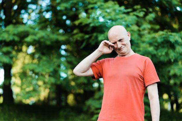 Закройте вверх по портрету старшего человека плача и смотрящего на камеру красными глазами. фото высокого качества